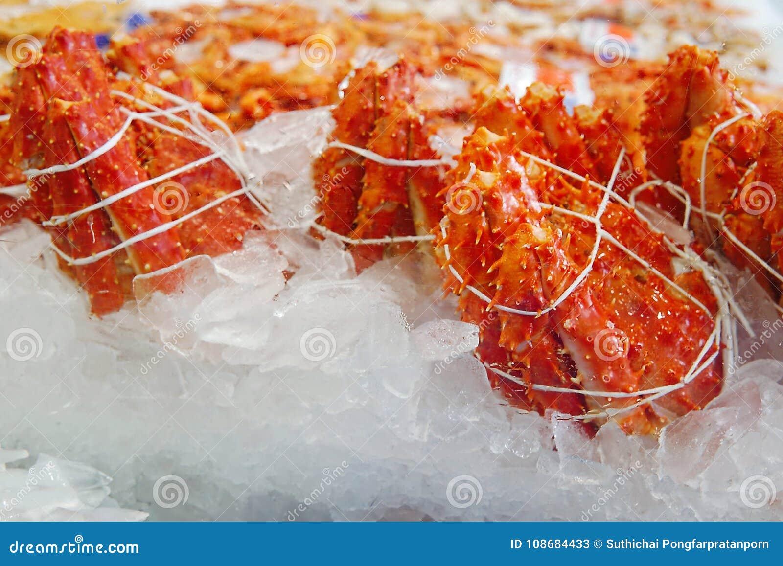 Selektiv fokus av konungkrabbabenet på is på fiskmarknaden Delen av konungkrabbabenet som är klart att sälja på skaldjur, shoppar
