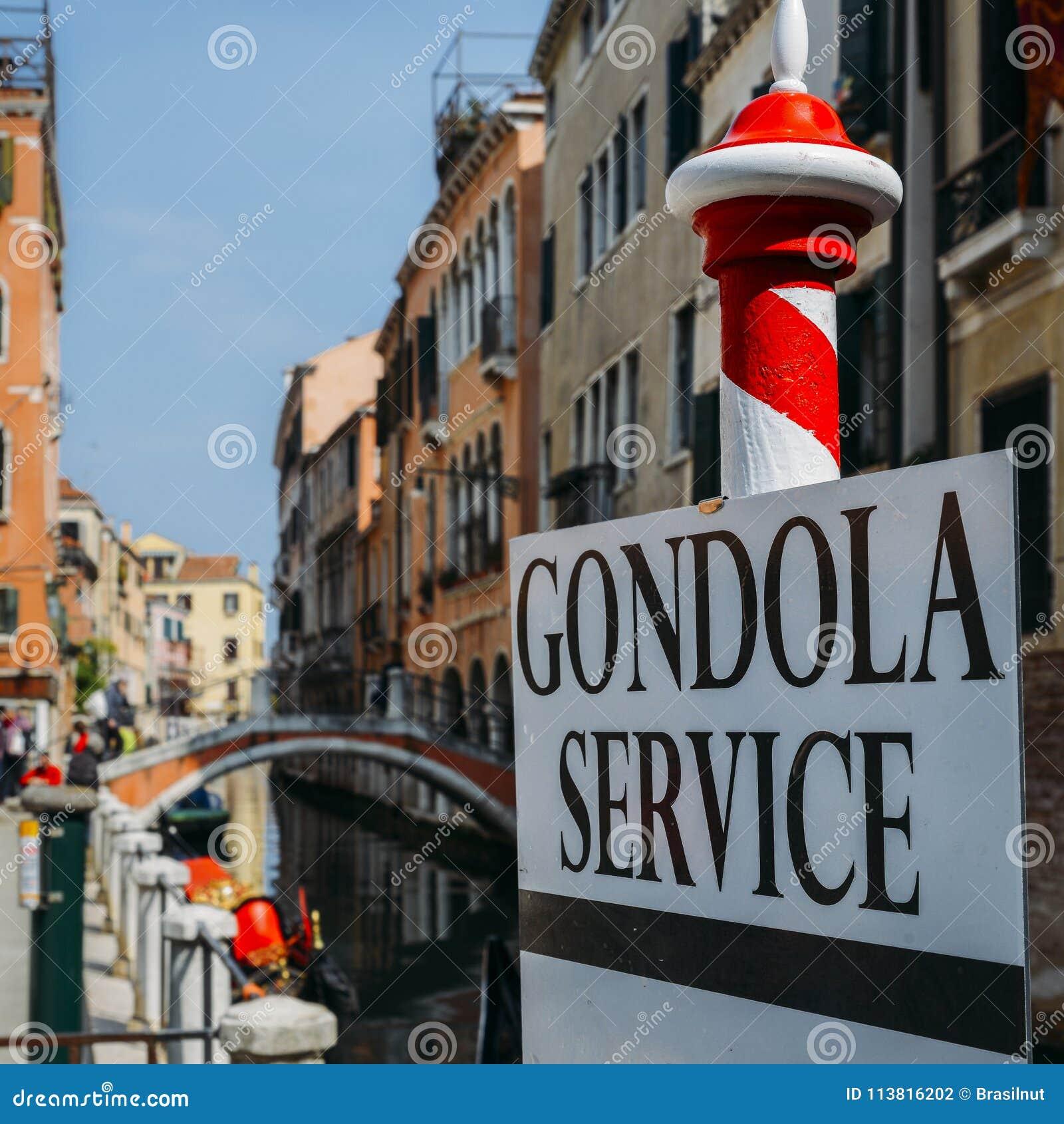 Selektiv fokus på traditionella röda och vita poler som annonserar gondolservice i Venedig