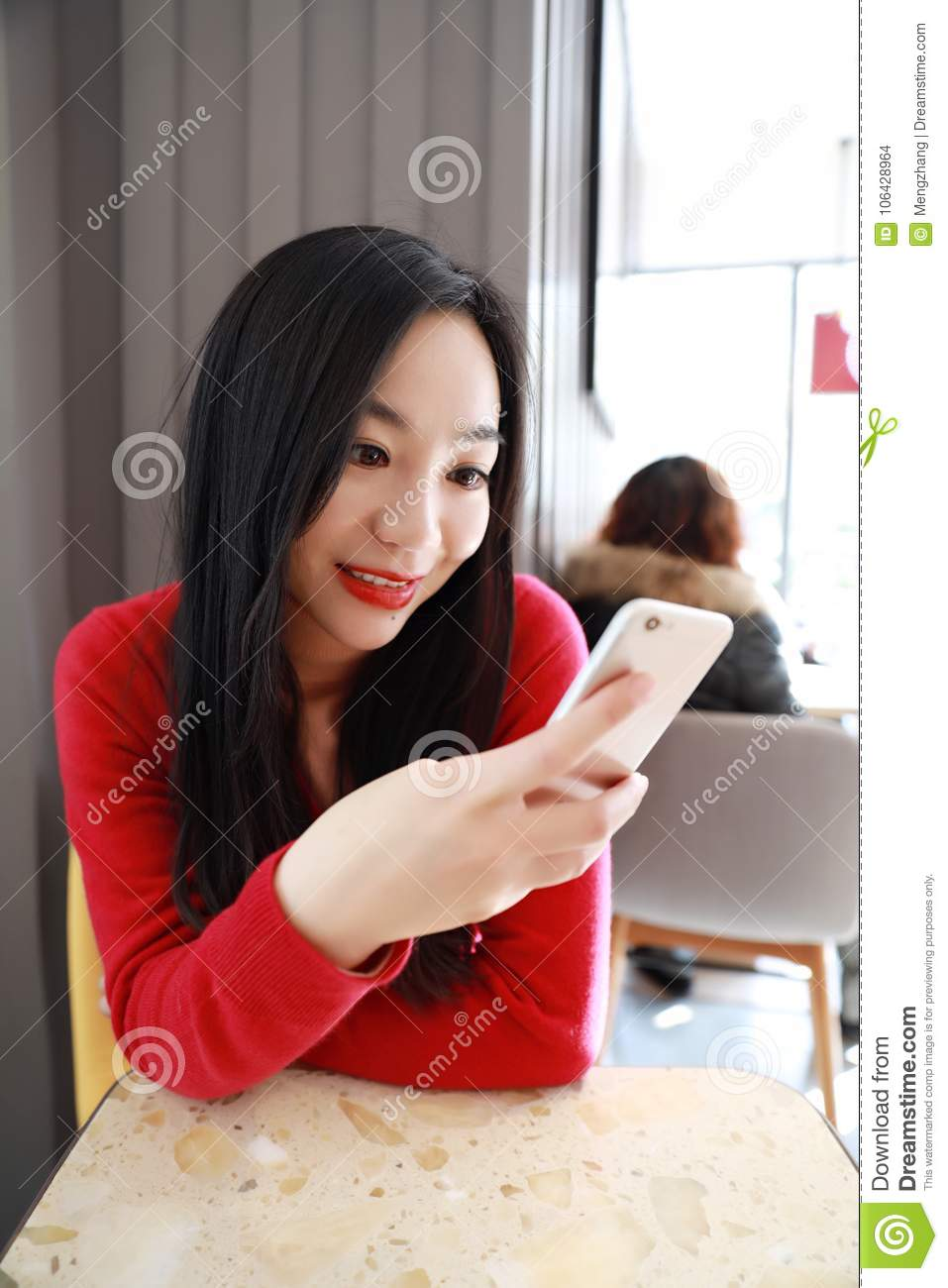Self employed china woman working with her phone and laptop in a restaurant