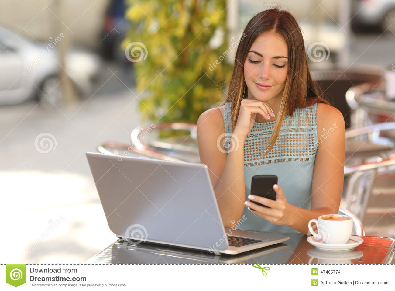 Self employed woman working with her phone and laptop in a restaurant