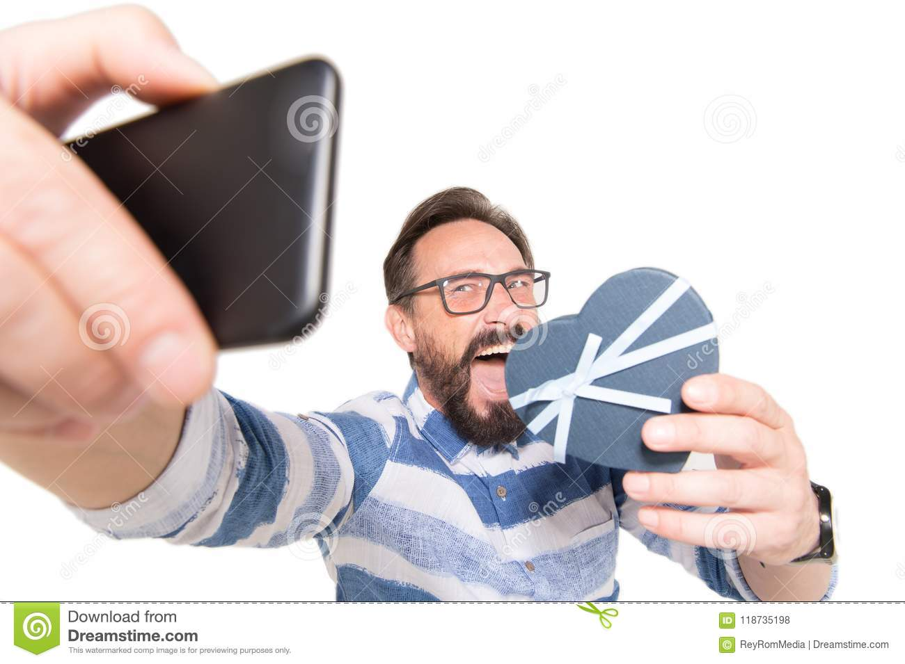 Selfie portrait of attractive, crazy bearded man in jeans shirt shooting selfie with heart over white background.
