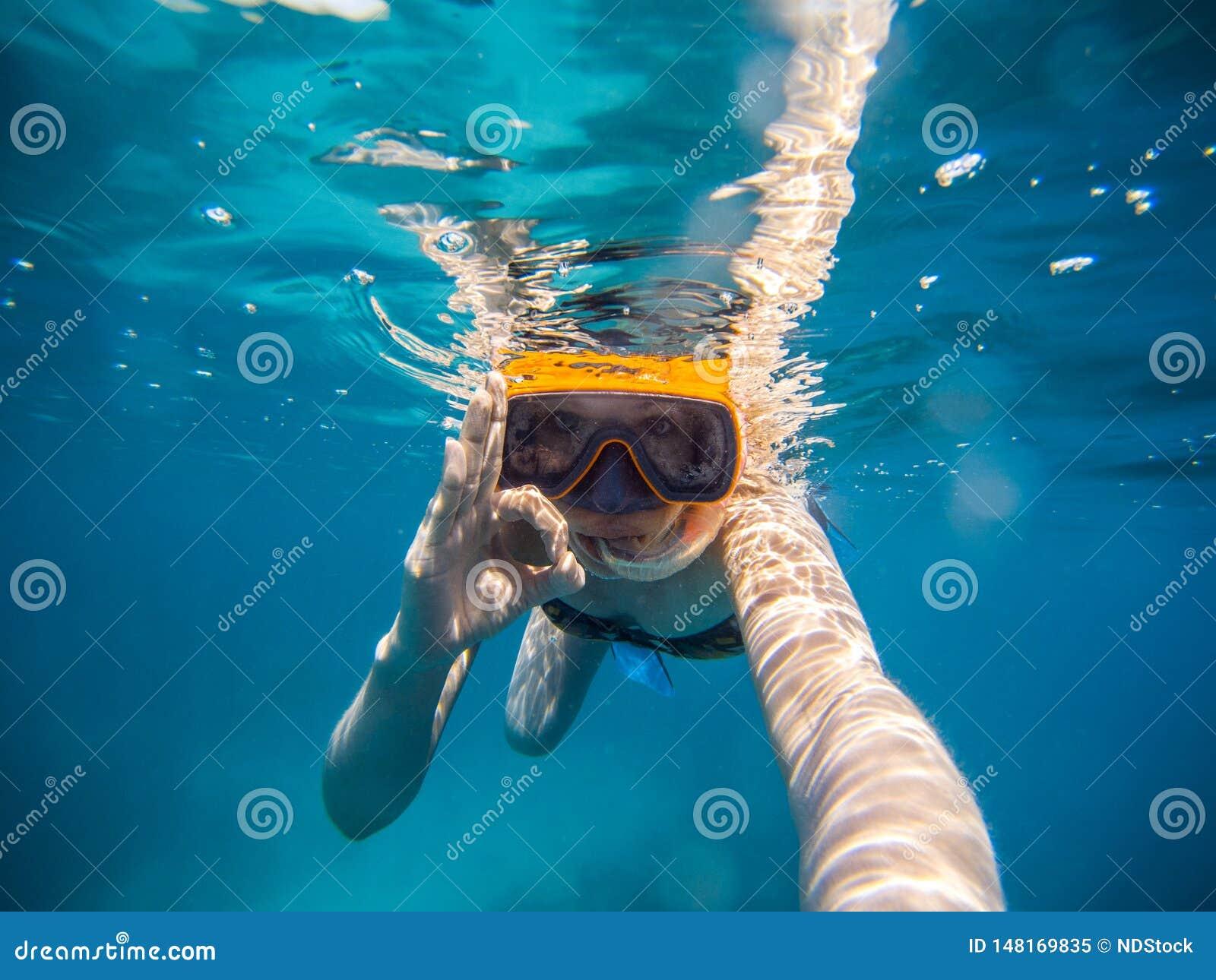 Selfie της νέας κολύμβησης με αναπνευστήρα γυναικών στη θάλασσα Κάνοντας όλα το εντάξει σύμβολο
