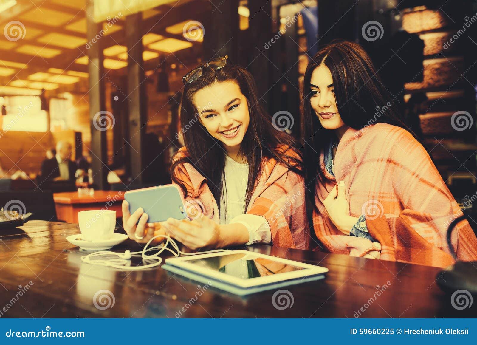 两个亲密的朋友做在咖啡馆的selfie