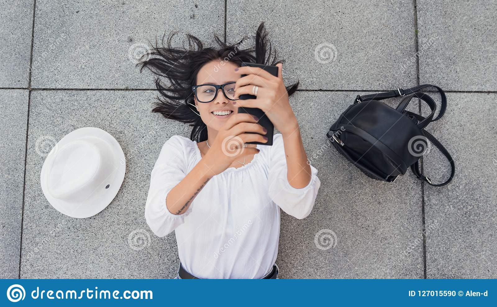 Selfie. Above viwe of young happy girl with smarthphone photographs yourself