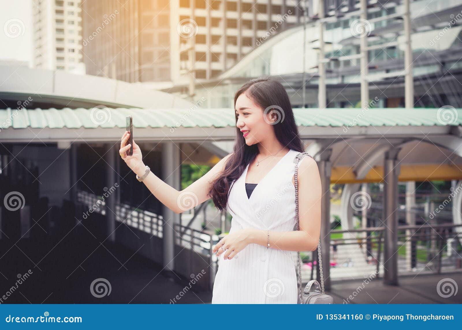 Selfie asiático hermoso de la mujer del retrato con el móvil y el caminar en la ciudad, confianza femenina feliz y sonrisa, conce