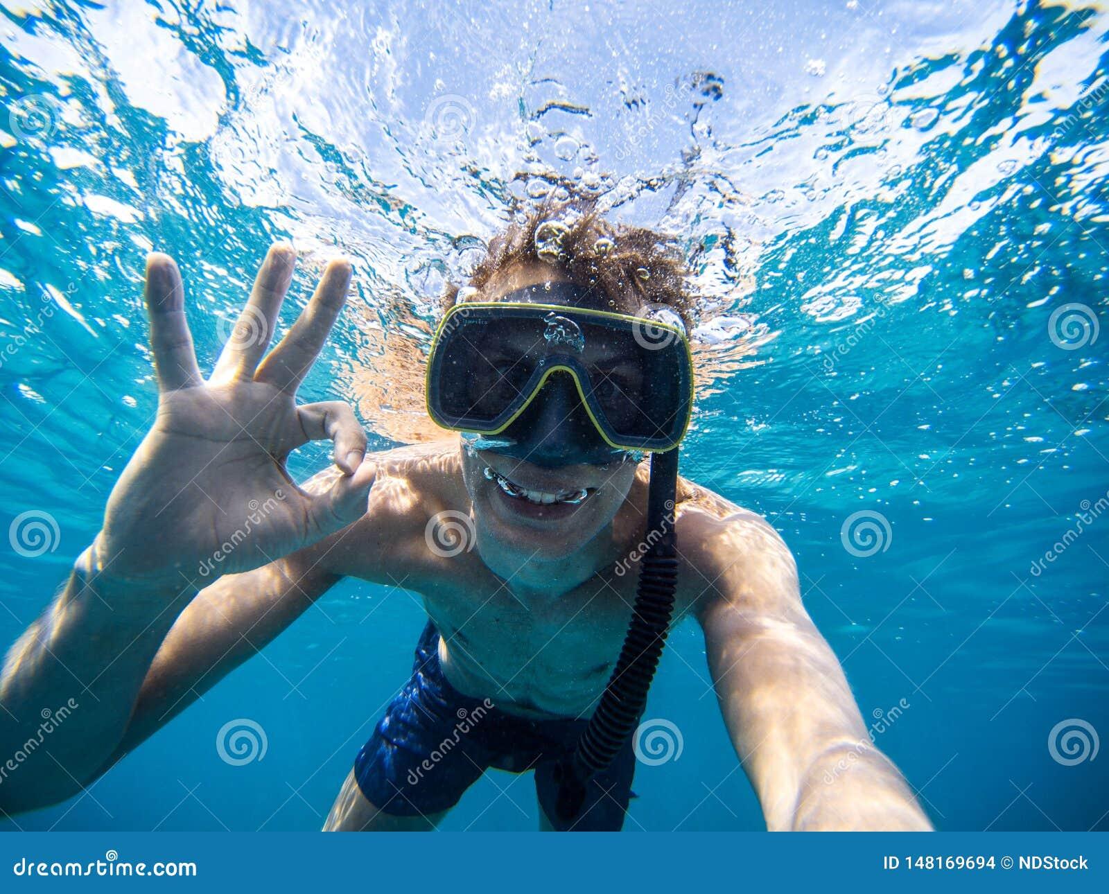 Selfie de jeune homme naviguant au schnorchel en mer Faisant à tout le symbole correct