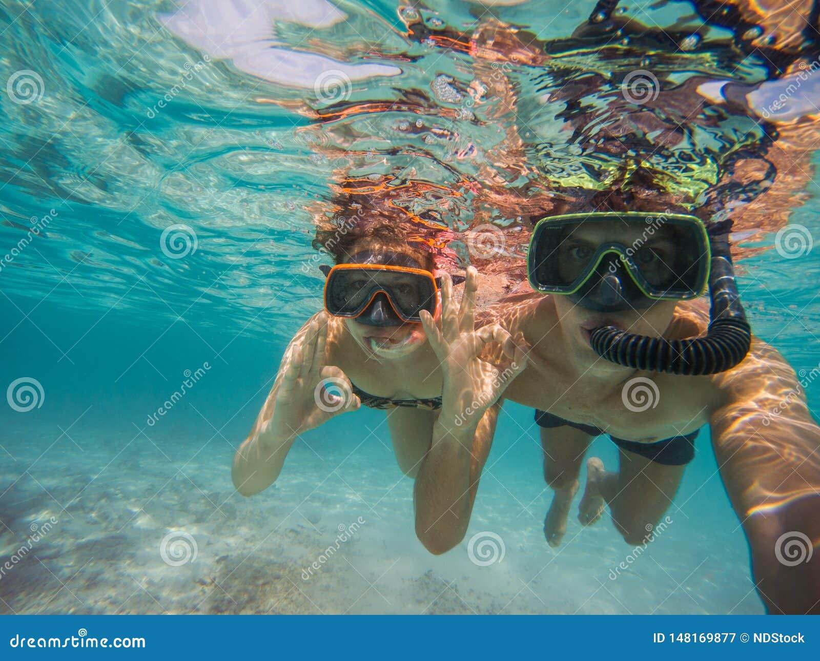 Selfie de los pares jovenes que bucean en el mar Haciendo todo s?mbolo aceptable