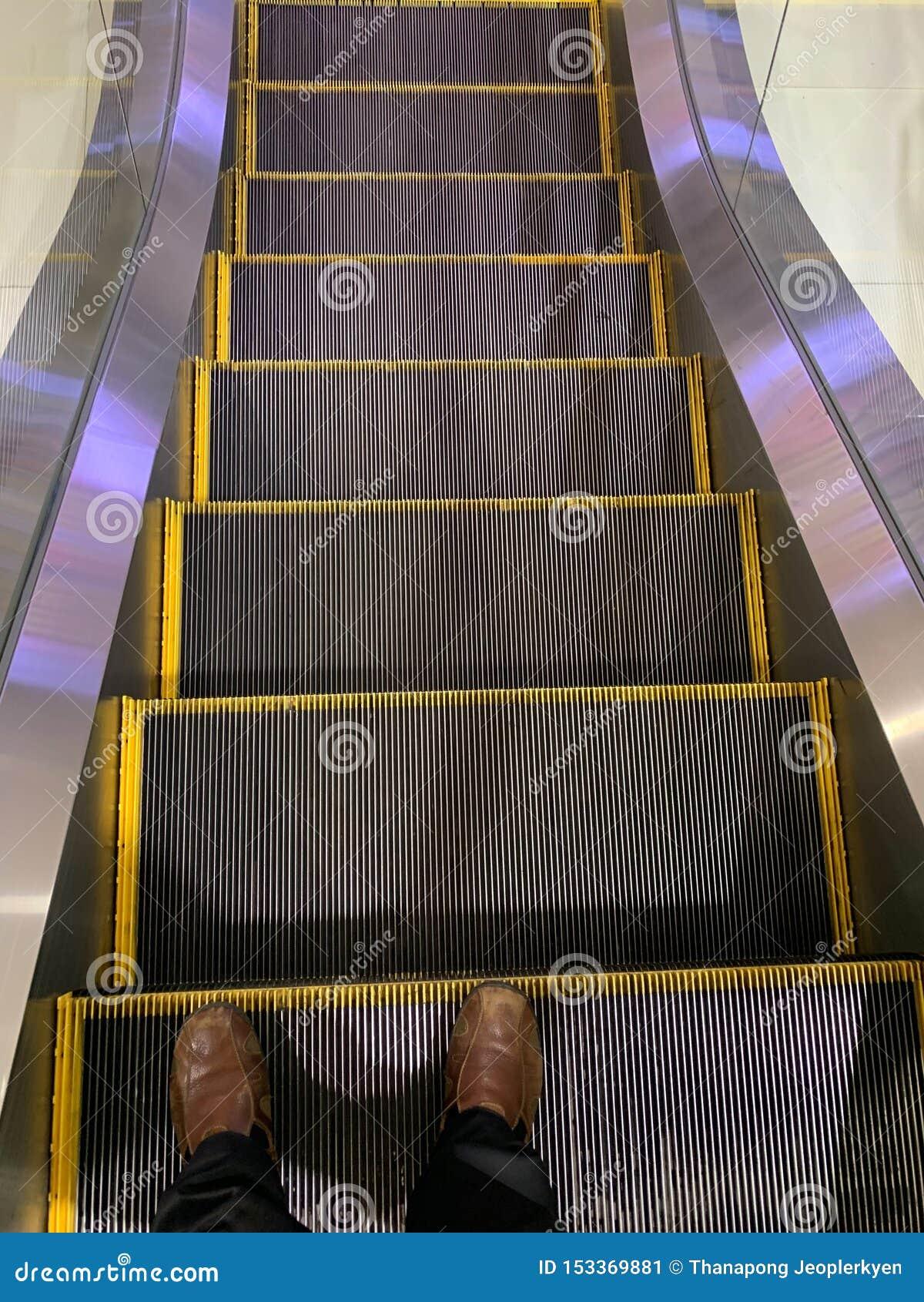Selfie de los pies del hombre en zapatos marrones en pasos de escalera móvil en el aeropuerto