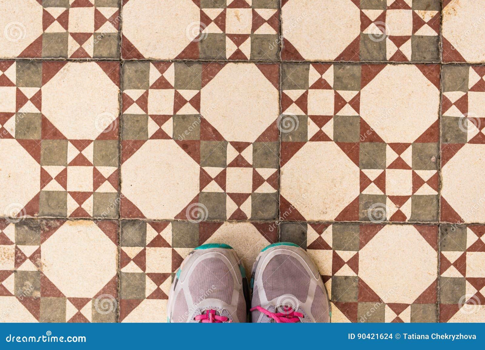 Selfie Of Feet With Sneaker Shoes On Art Pattern Tiles Floor Top View