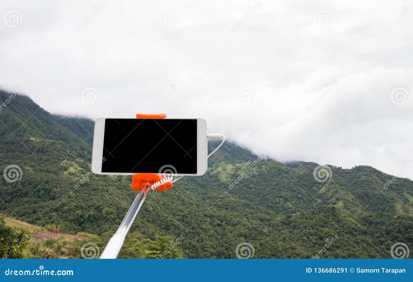 Selfie fotobegrepp: Extensible selfiepinne eller monopod med mobiltelefonen som tar bilden som skjutas på den utomhus- bergsikten