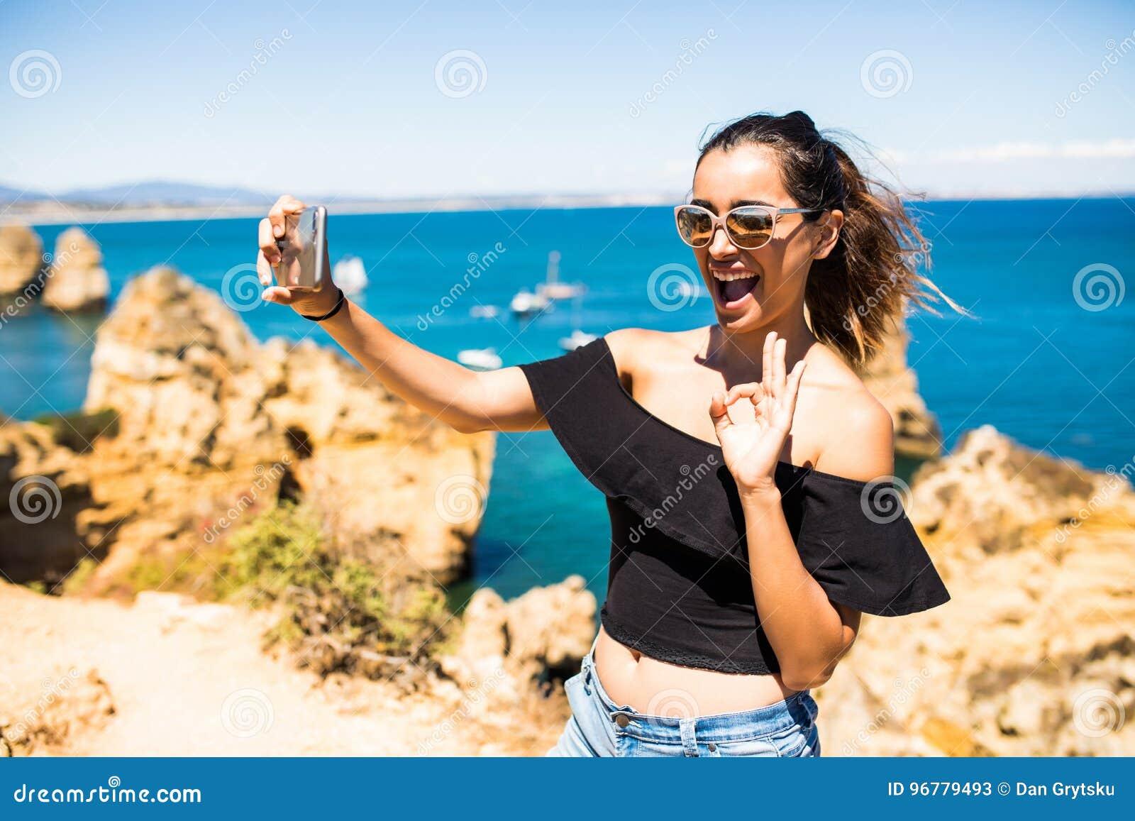 Selfie latino de la toma de la mujer de la belleza del teléfono en la cima del acantilado hermoso s y de rocas de Océano Atlántic