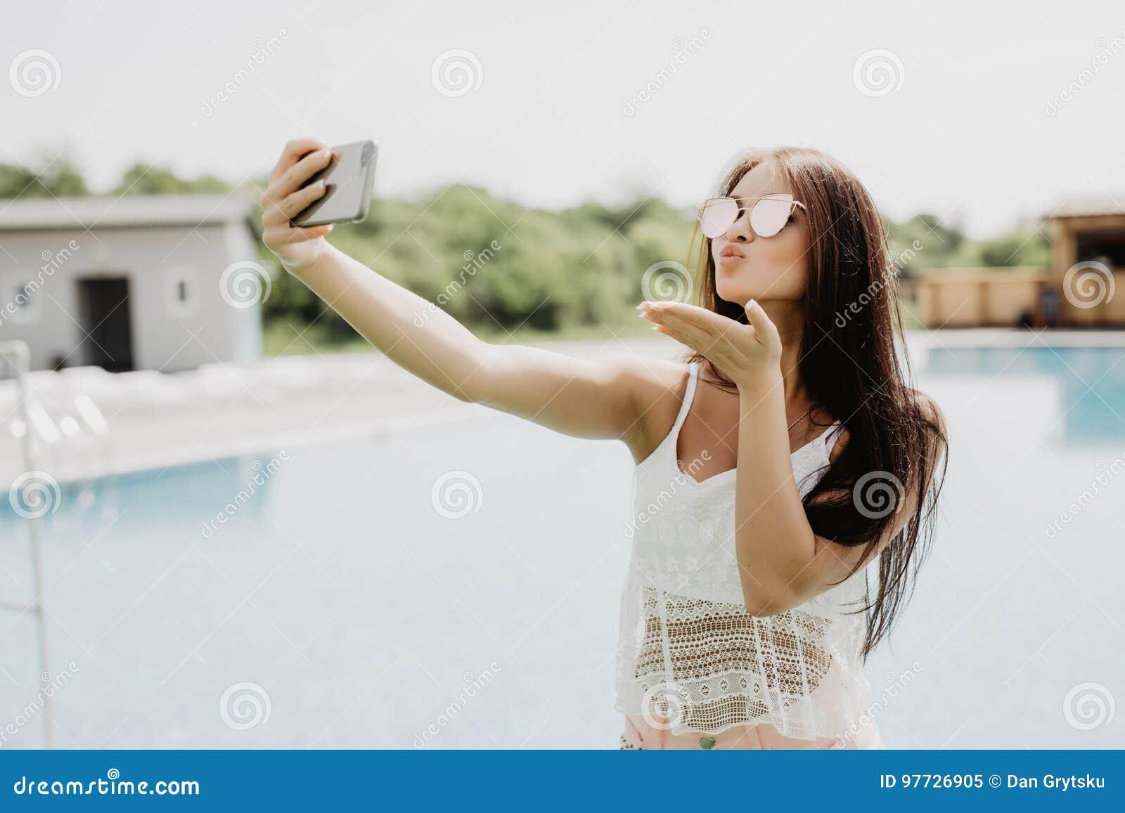 Selfie-retrato do close-up da menina moreno atrativa com o cabelo longo que está a associação próxima Veste o t-shirt cor-de-rosa