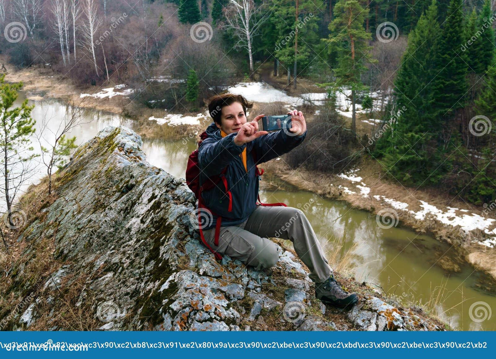 Selfie sobre um penhasco acima do rio da mola