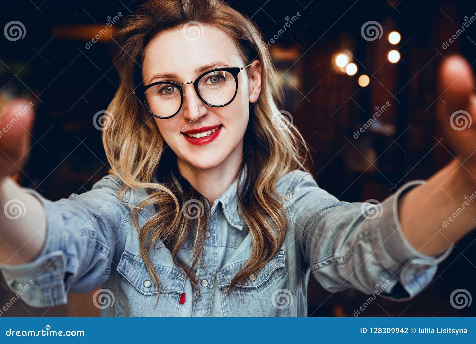 Selfie stående av barn som ler kvinnasammanträde i kafé Hipsterflickan i moderiktiga exponeringsglas tar en selfie i coffee shop