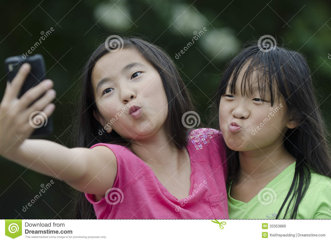 Two beautiful asian girls talking a self portrit with a camera phone