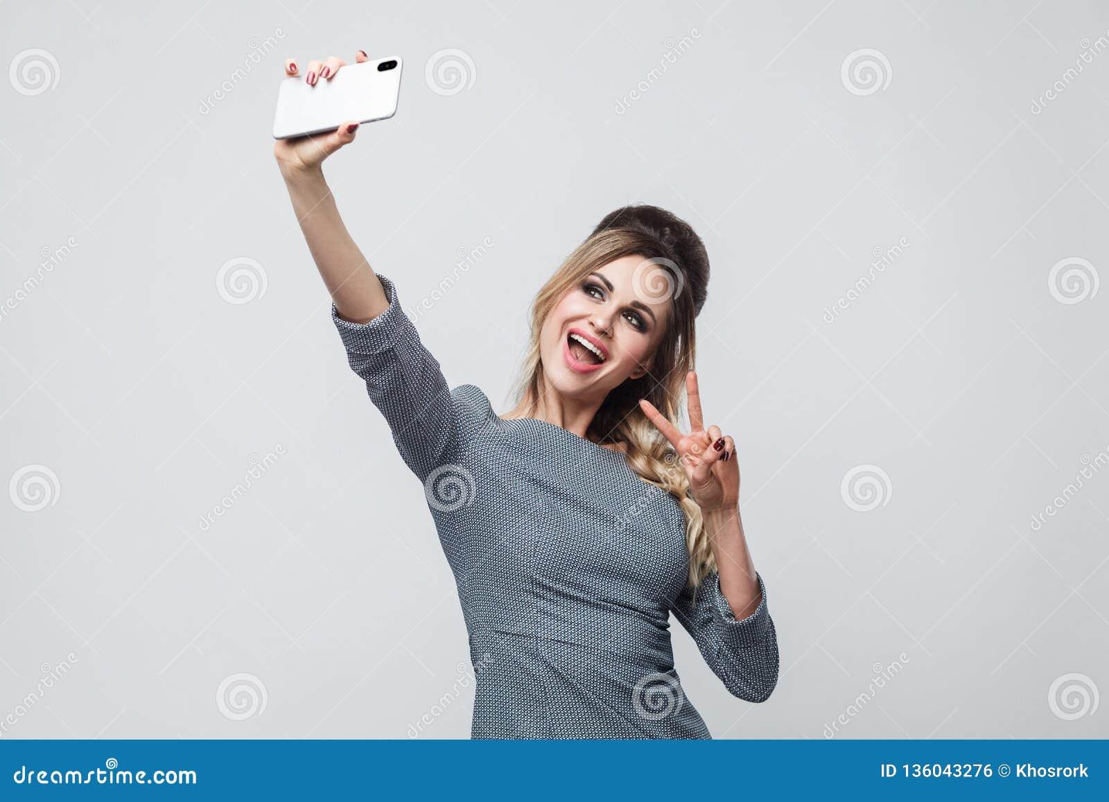 Selfietijd! Het gelukkige mooie bloggertiener dragen in grijze kleding met vlecht bij de hoofd status, die v tonen zingt met toot