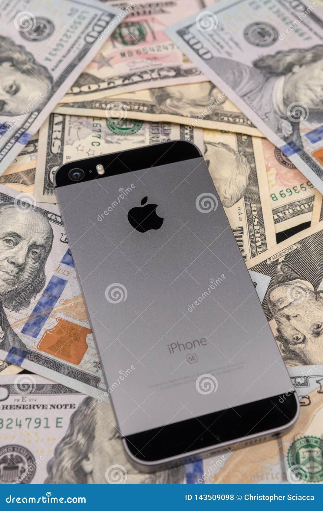 Selinsgrove, PA, U.S.A. - 31 marzo 2019: Un iPhone di Apple si siede sopra un mucchio di valuta degli Stati Uniti