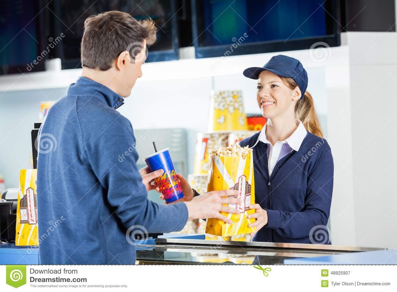 worker selling popcorn to man at concession stand stock photo seller giving popcorn and drink to man at royalty stock photography