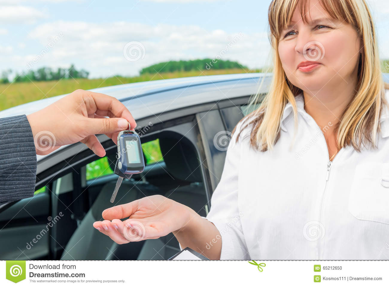 seller presents the woman key from the new car