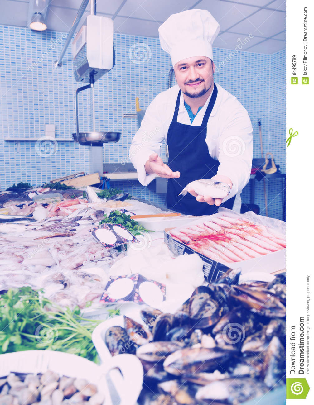 Seller in black apron showing fish stock image for White cap fish