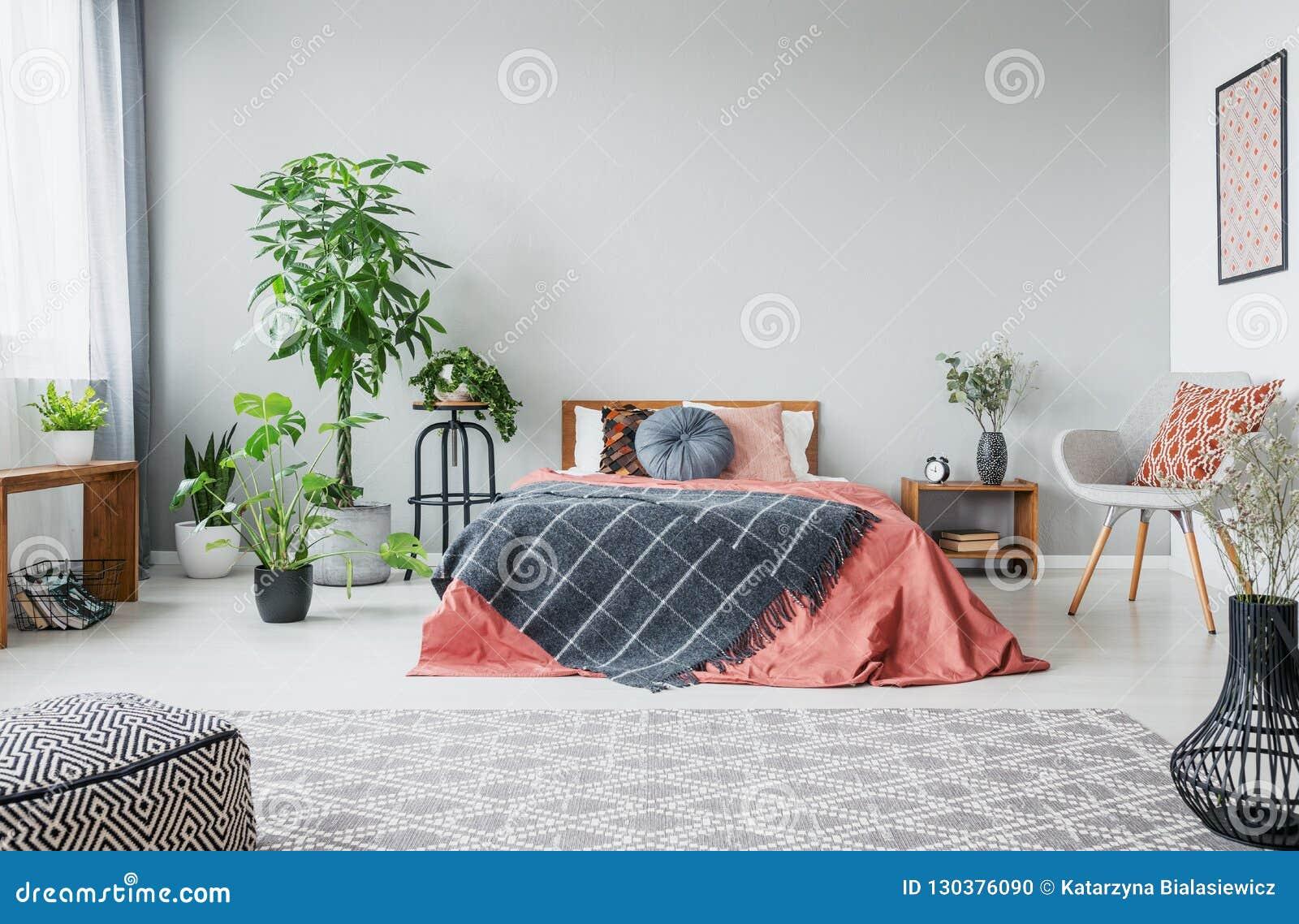 Selva urbana en dormitorio moderno con la cama gigante, la butaca gris cómoda y la alfombra modelada