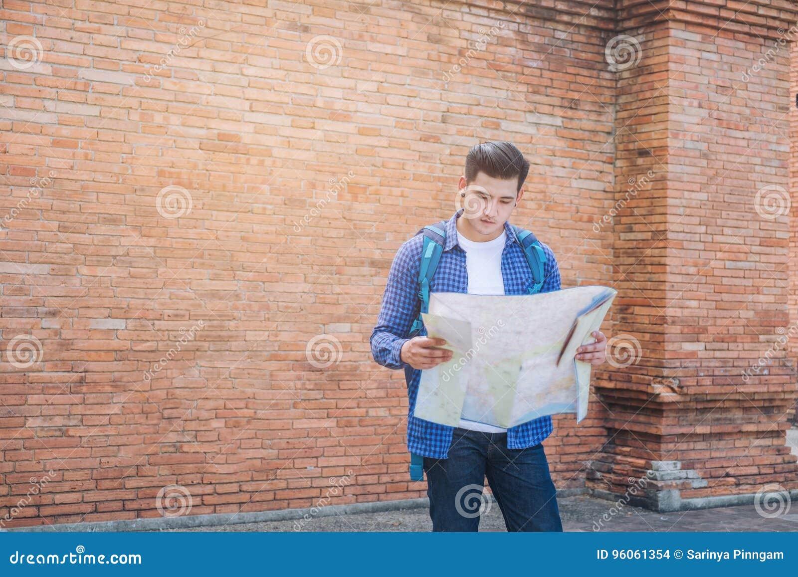 Sembler à la mode d homme de voyage recherchant la direction sur la carte de site tandis que