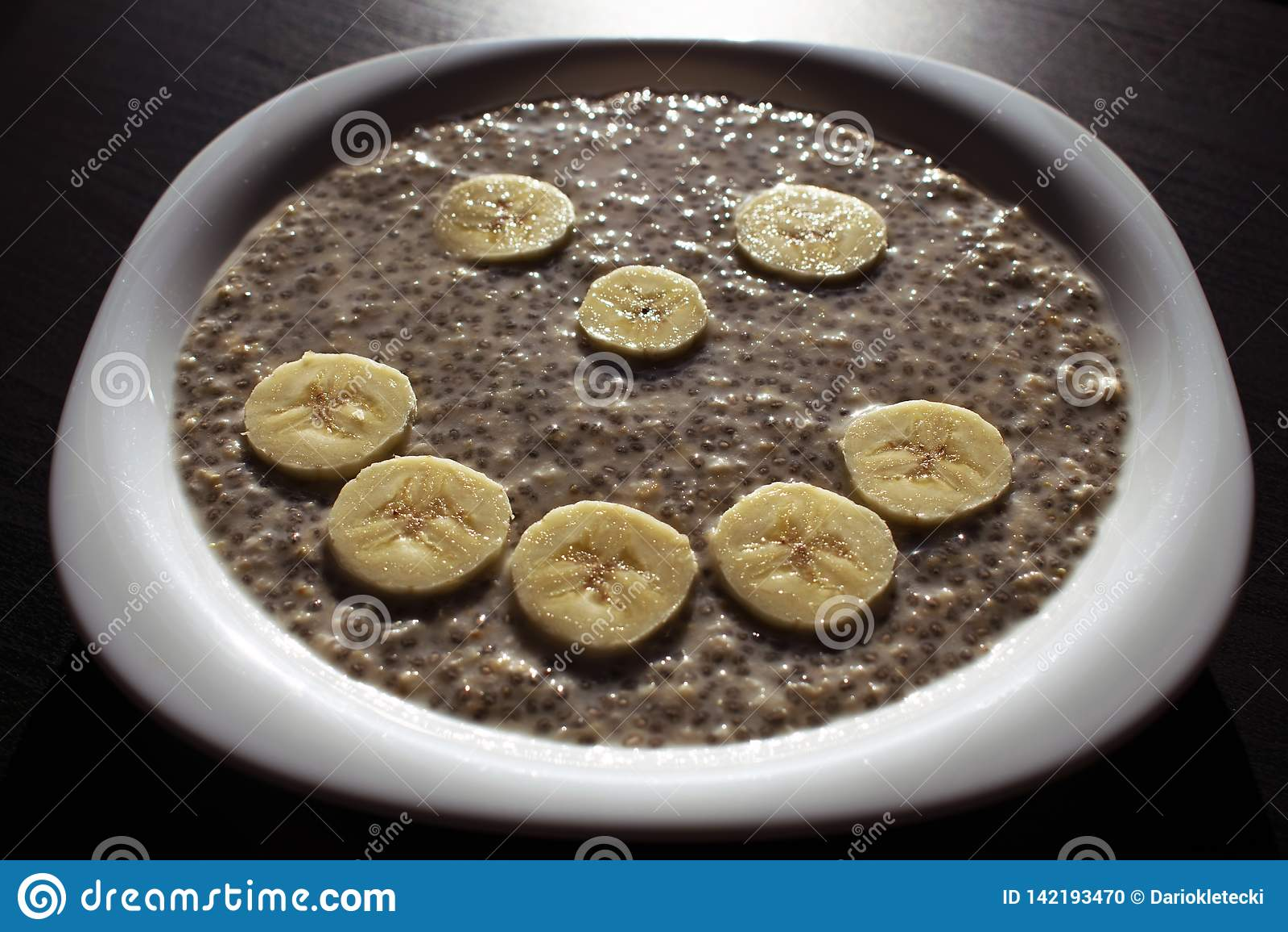 Sementes de Chia e flocos da aveia na água, com as fatias da banana arranjadas na cara do smiley em uma placa branca