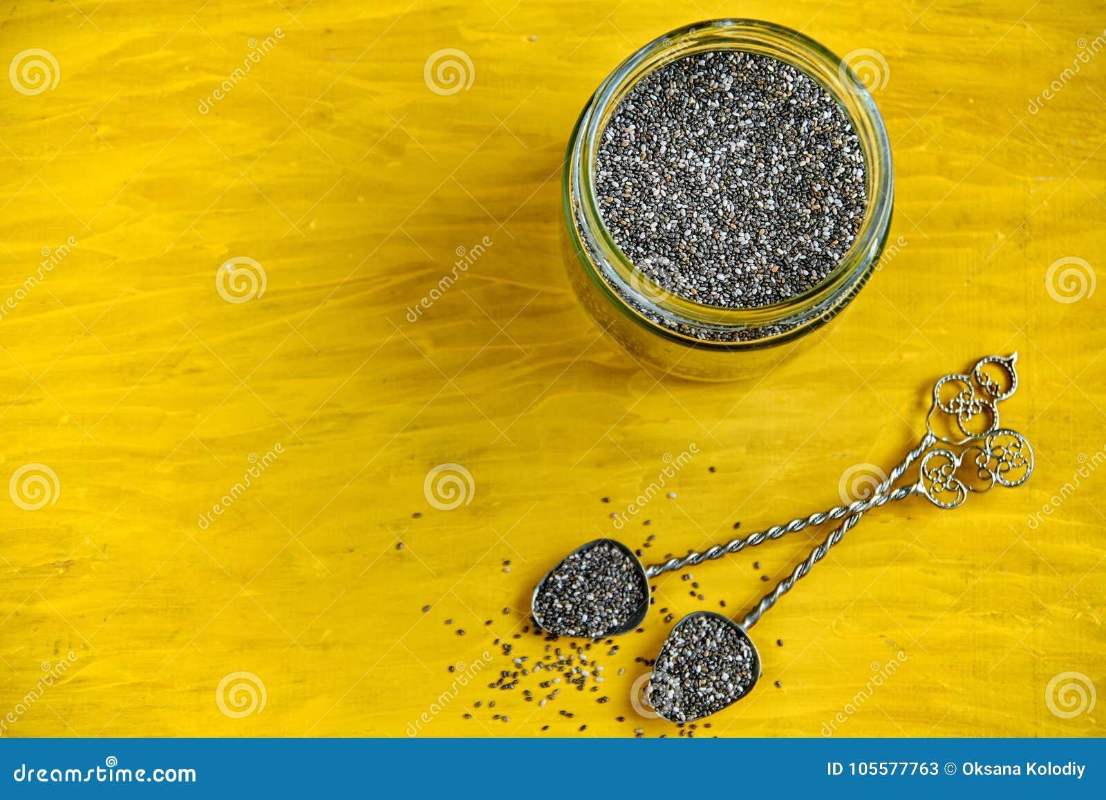 Sementes frescas do chia no fundo de madeira amarelo com espaço da cópia gratuita Colheres do vintage e frasco de vidro com chia