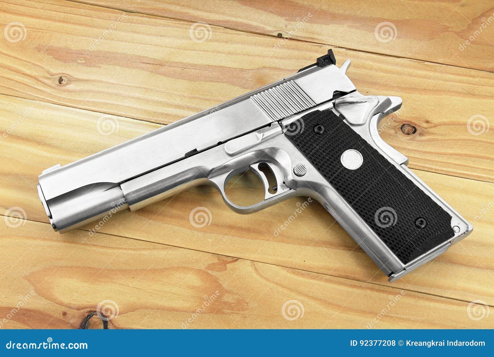 Semi-automatic handgun on grey wooden background, .45 pistol.