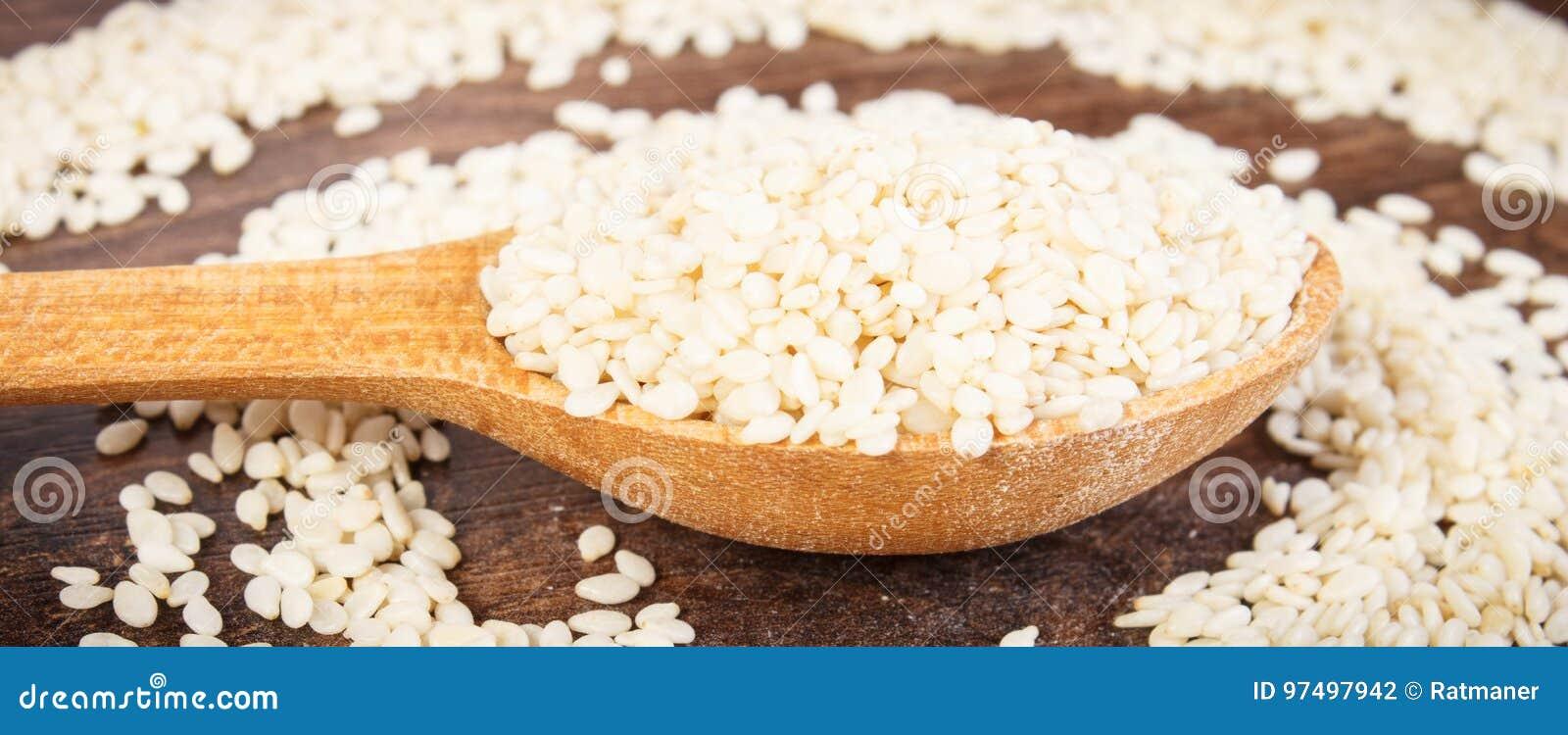 Semi di sesamo con il cucchiaio sul bordo rustico, concetto sano di nutrizione