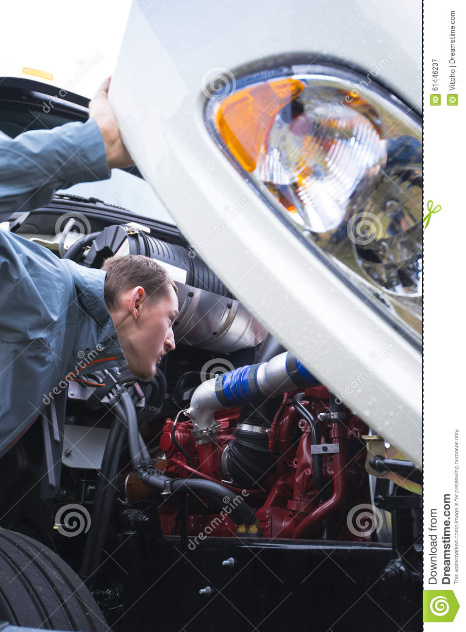 Semi Truck Driver Inspect Working Engine Of White Big Rig