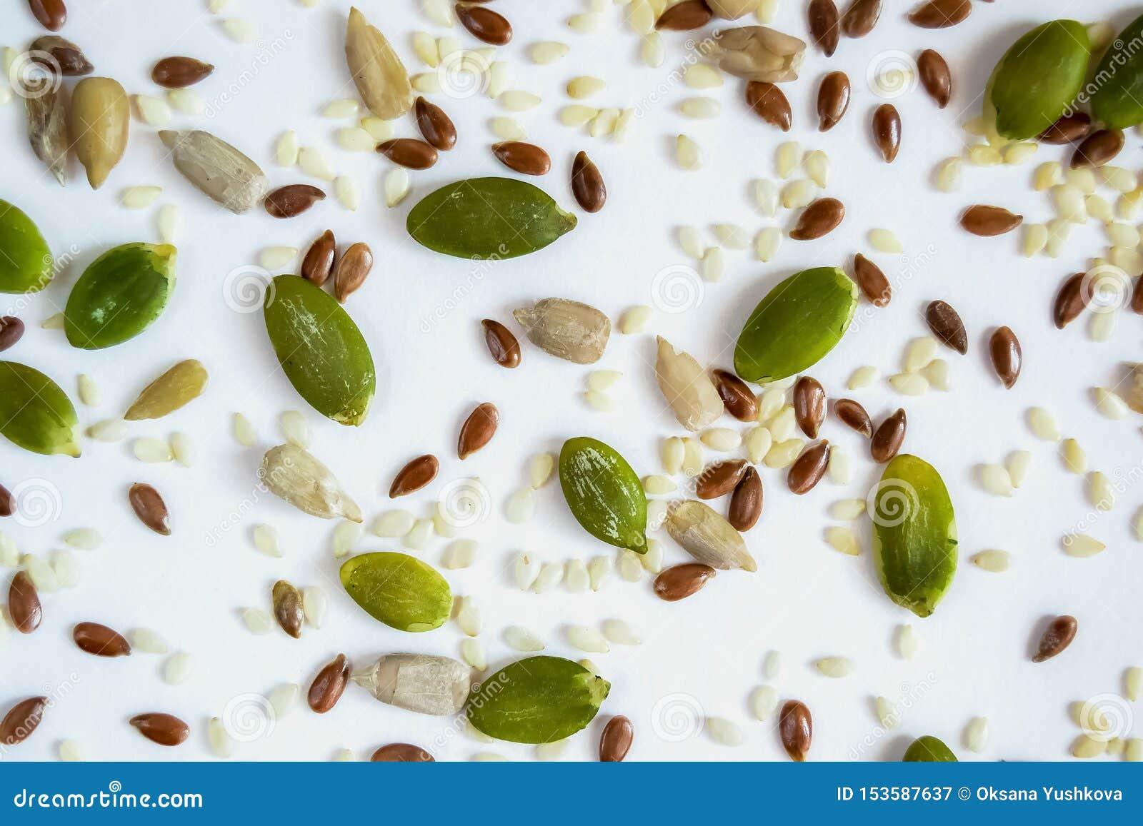 Semillas de lino derramadas de la calabaza y del girasol en un fondo blanco