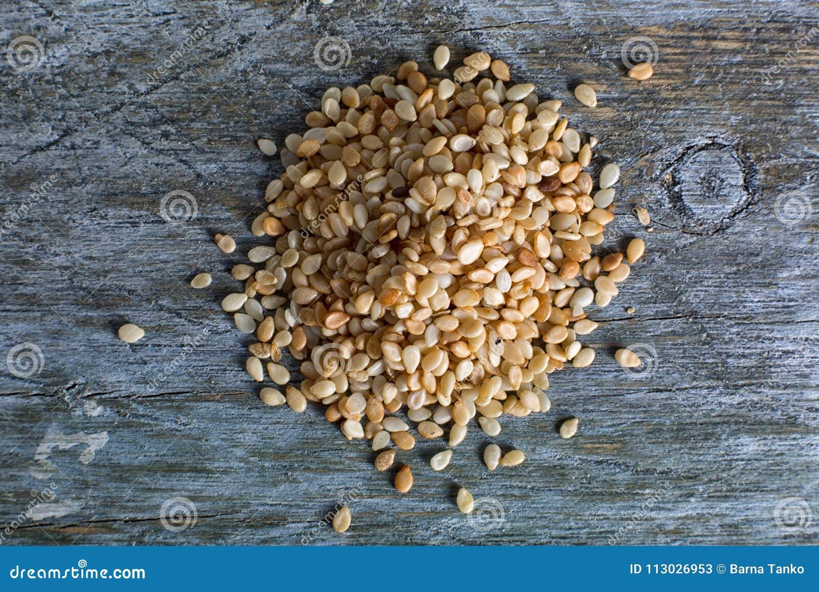 Semillas de sésamo en superficie de madera rústica