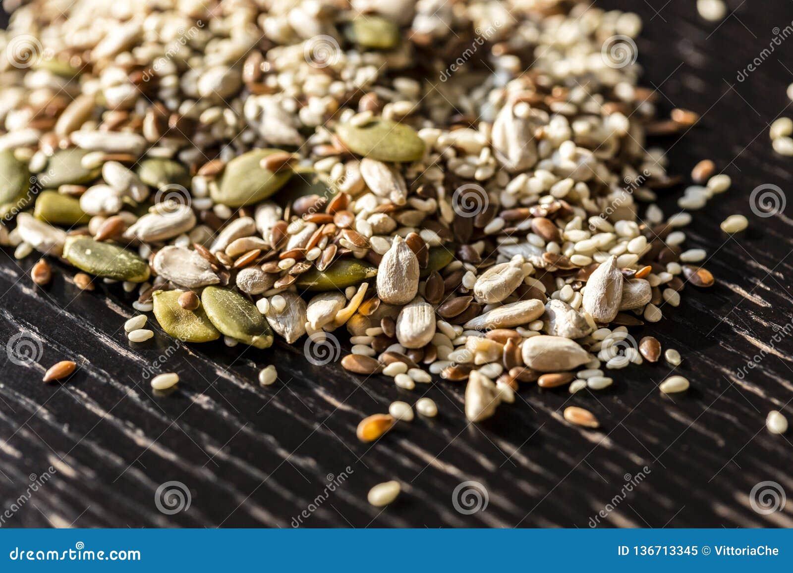 Semillas secas mezcladas calabaza, sésamo, girasol, lino para la consumición sana en la tabla negra de madera