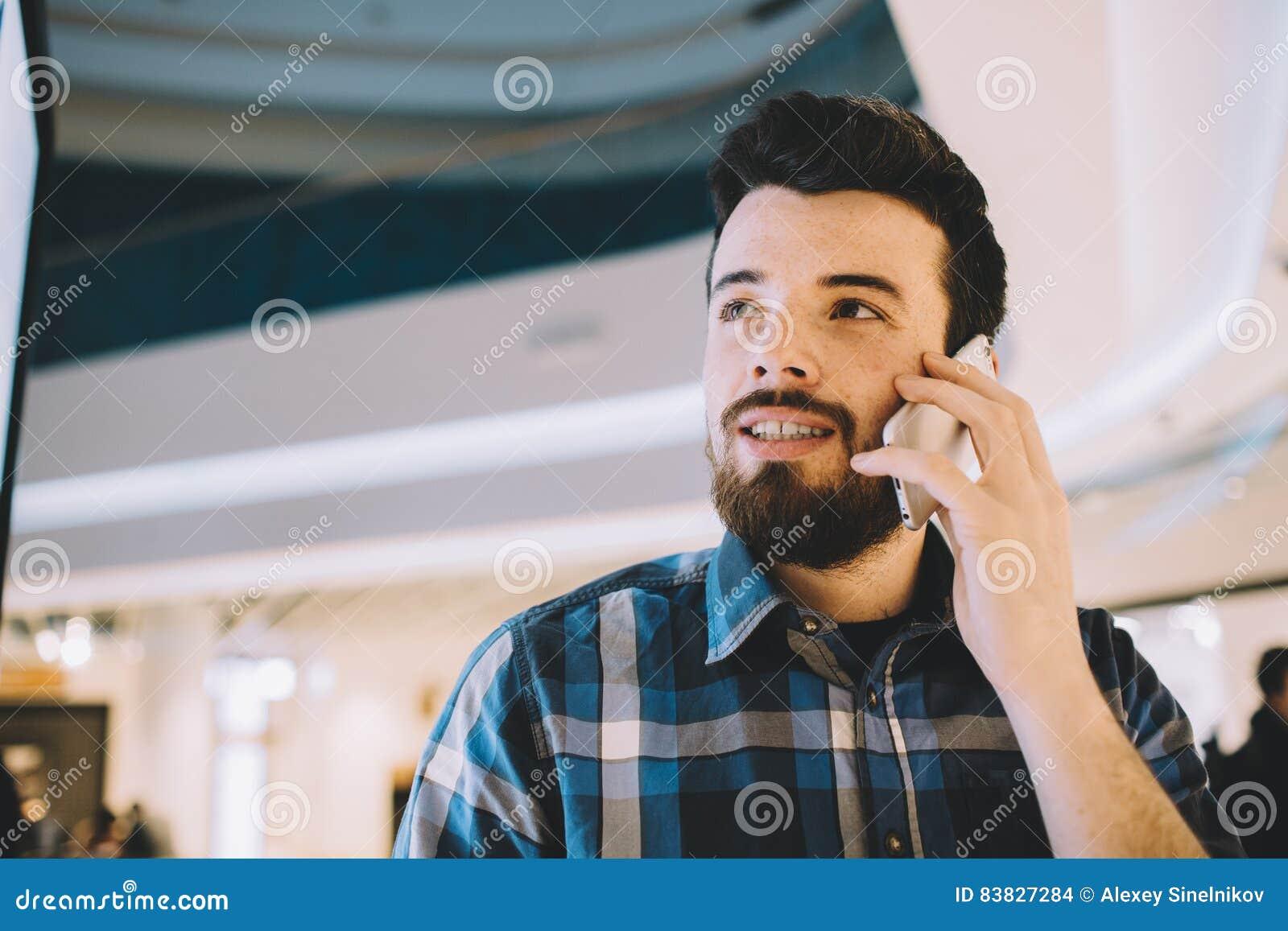 Sempre in tocco Giovane bello sorridente che parla sul suo telefono