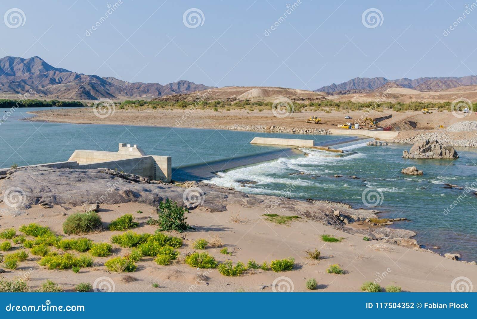 Sendelingsdrif, Namíbia - 10 de julho de 2014: Construção concreta da represa no rio, na beira África do Sul e em Namíbia alaranj