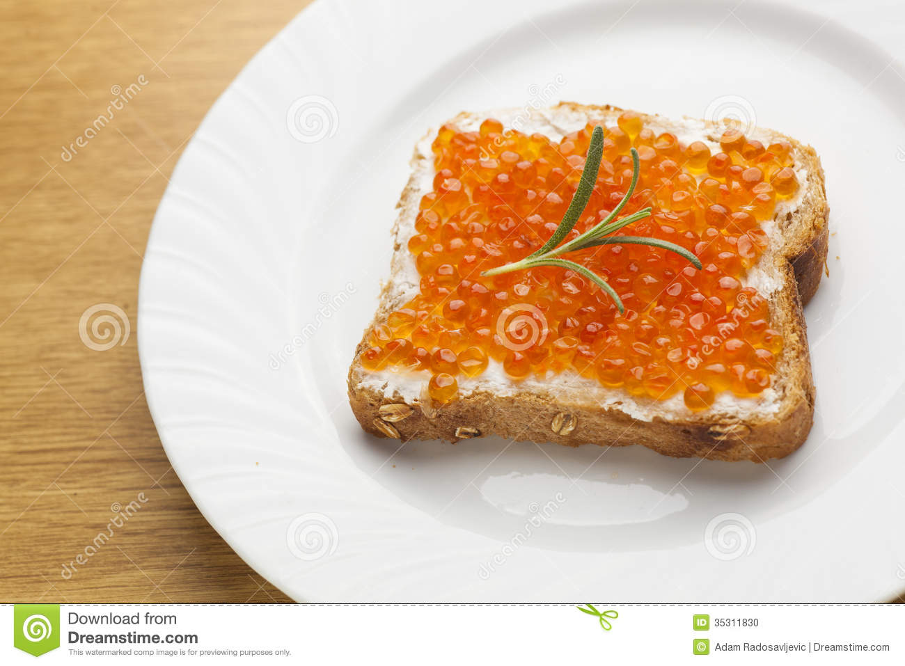 Sendwich with caviar on bread decorated with rosemery for Fish eggs food