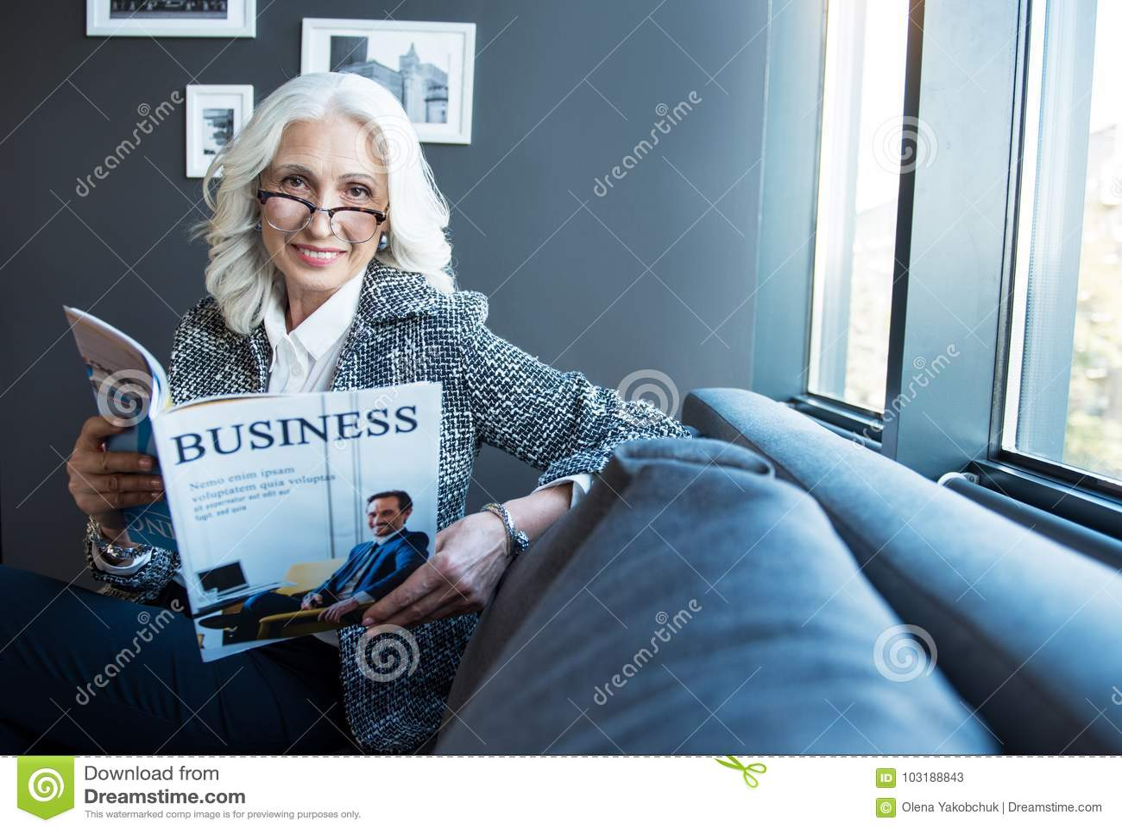 A senhora à moda otimista encantador está descansando com jornal