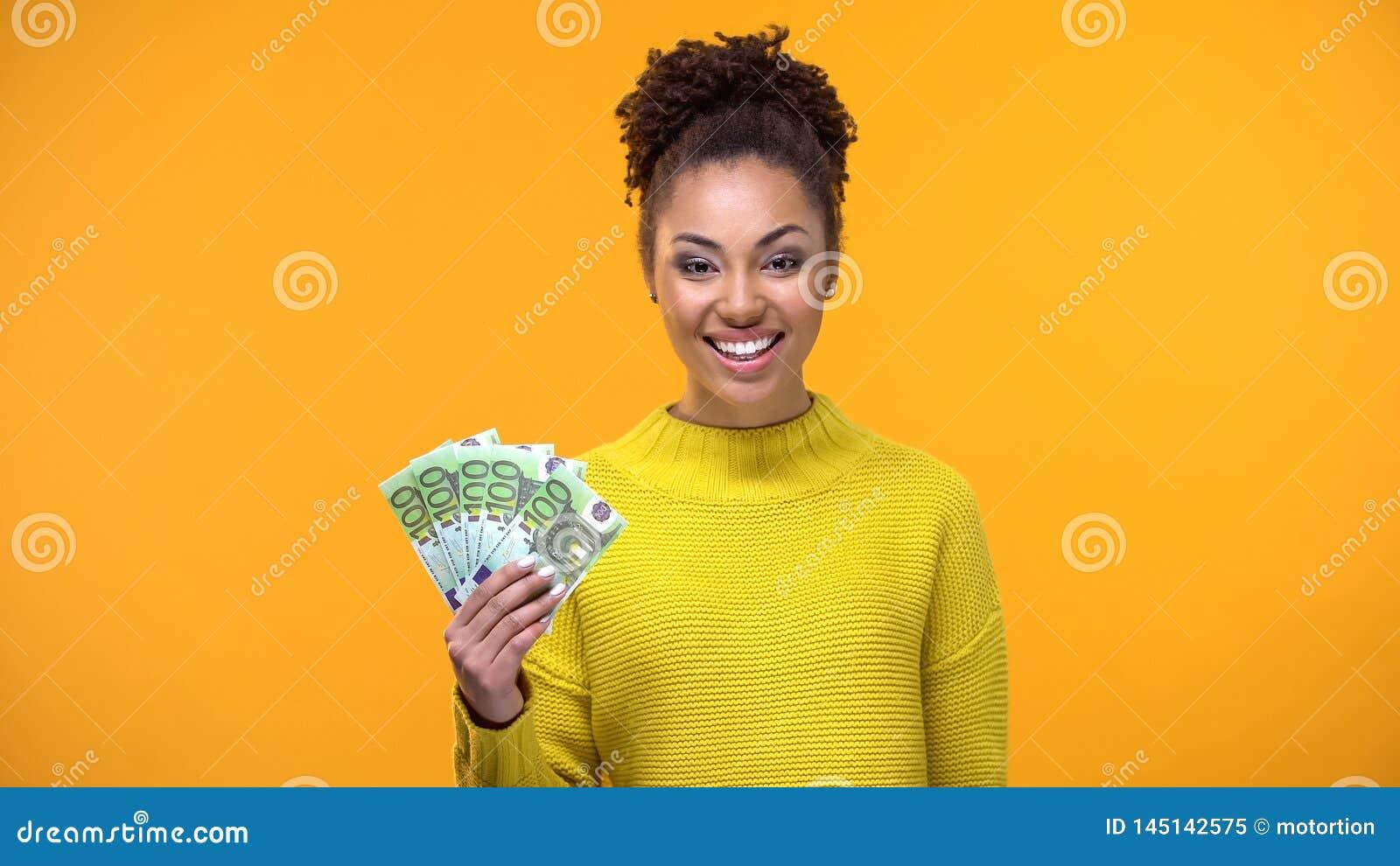 Senhora afro-americano de sorriso que mostra o grupo dos euro ? c?mera, trabalho alto-pago