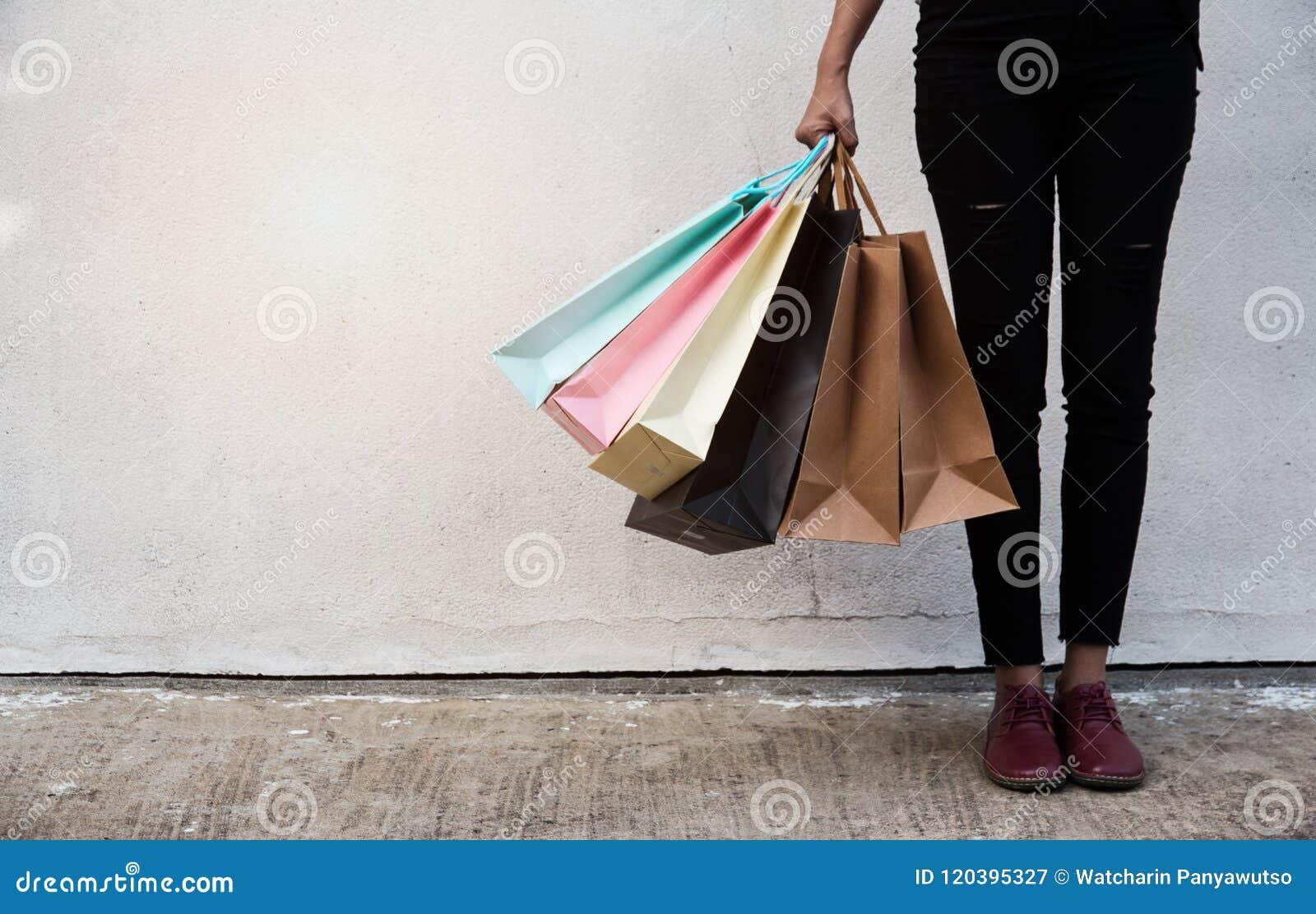 A senhora está guardando sacos de compras coloridos em seu assistente, ela está estando na frente da parede do cimento, após a co