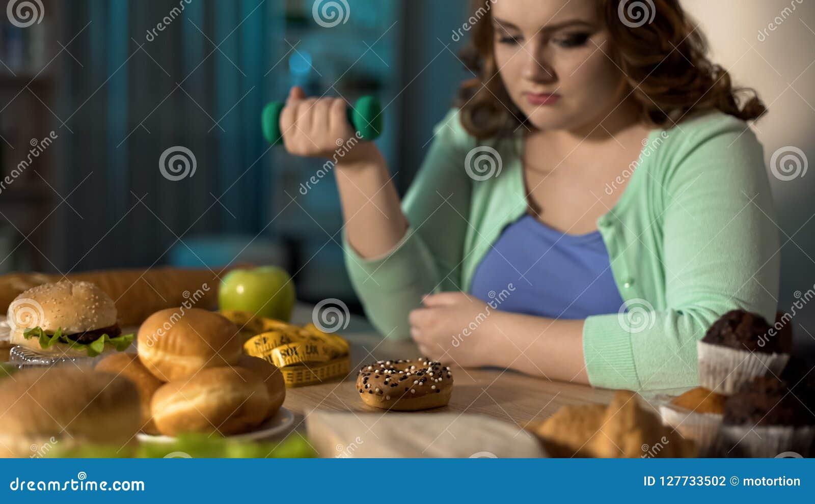 Senhora excesso de peso que exercita e que olha tristemente a comida lixo, problema da obesidade