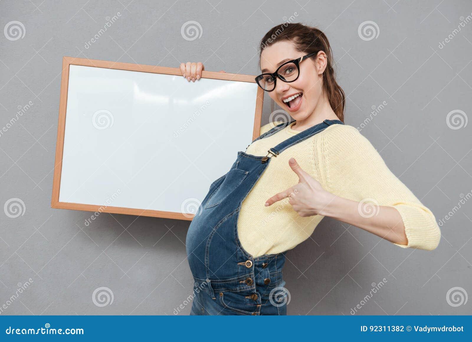 Senhora feliz grávida que guarda a placa e apontar do copyspace
