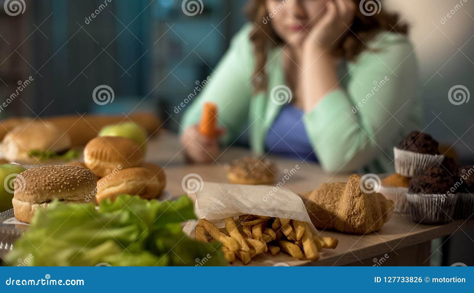 Senhora gorda deprimida que senta-se na tabela completamente da comida lixo insalubre, comendo demais