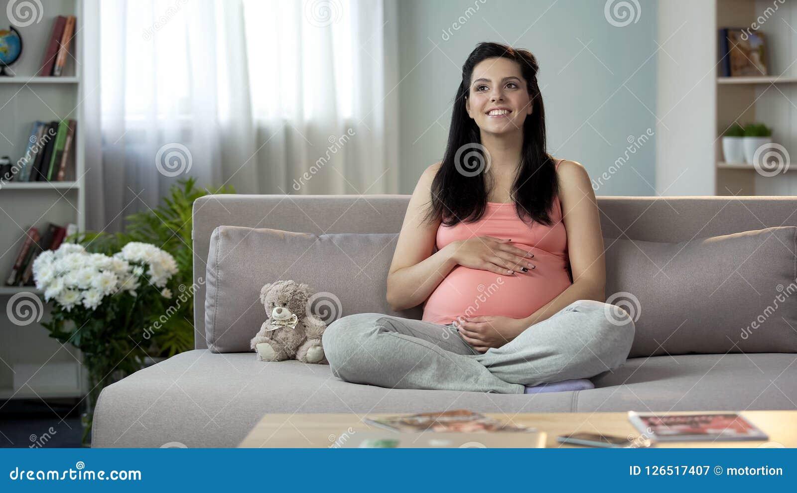 Senhora grávida inspirada que afaga a barriga, sonhando o mais logo da aparência de recém-nascido