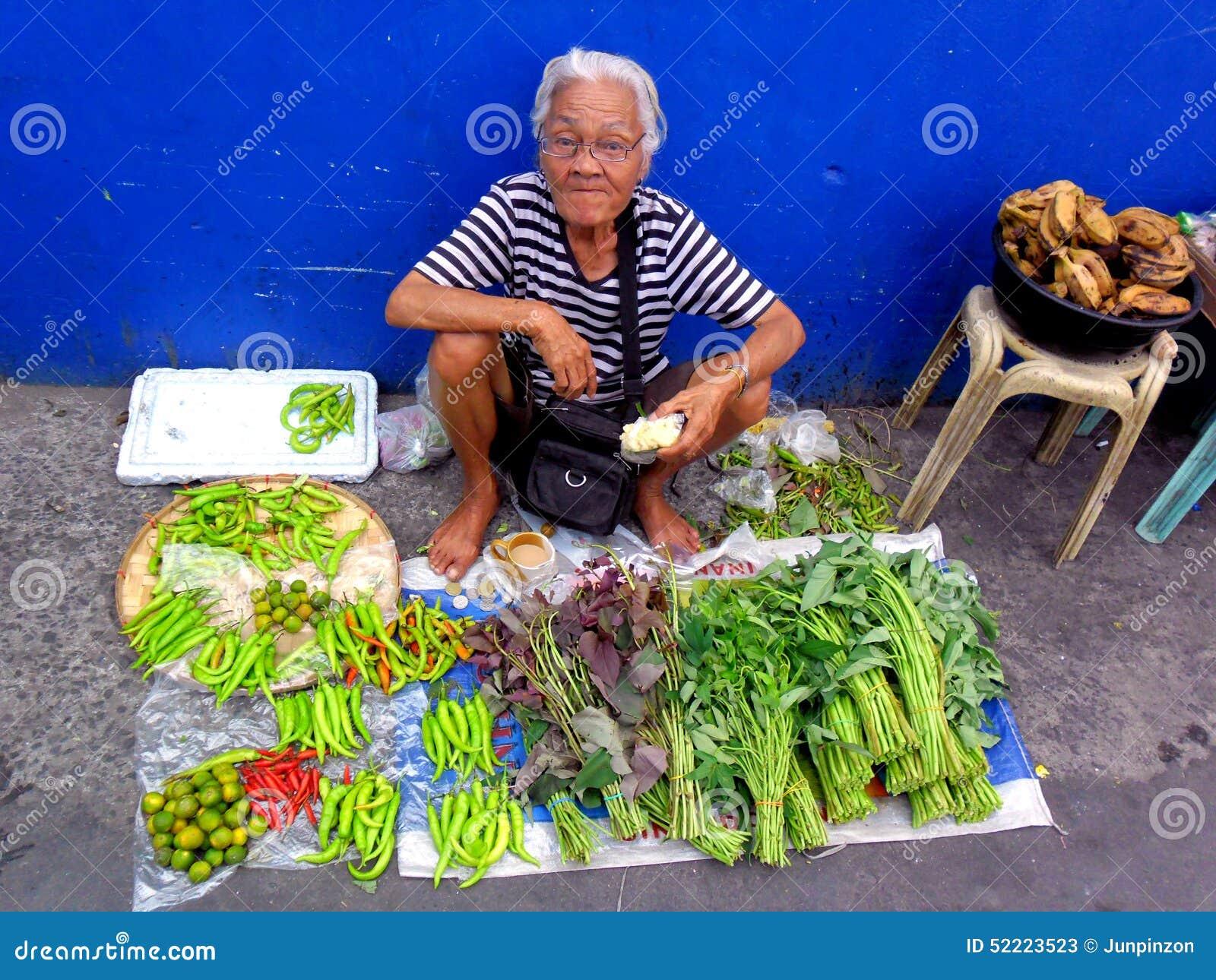 Senhora idosa em um mercado do cainta, rizal, Filipinas que vendem frutas e legumes