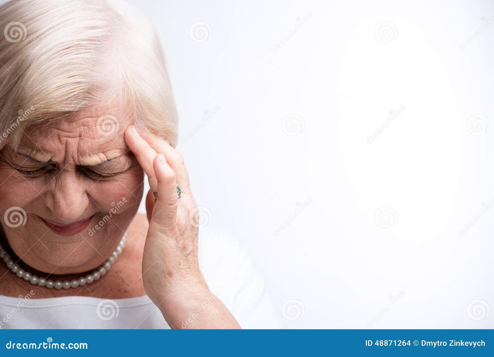Senhora idosa que toca em sua cabeça com dedos