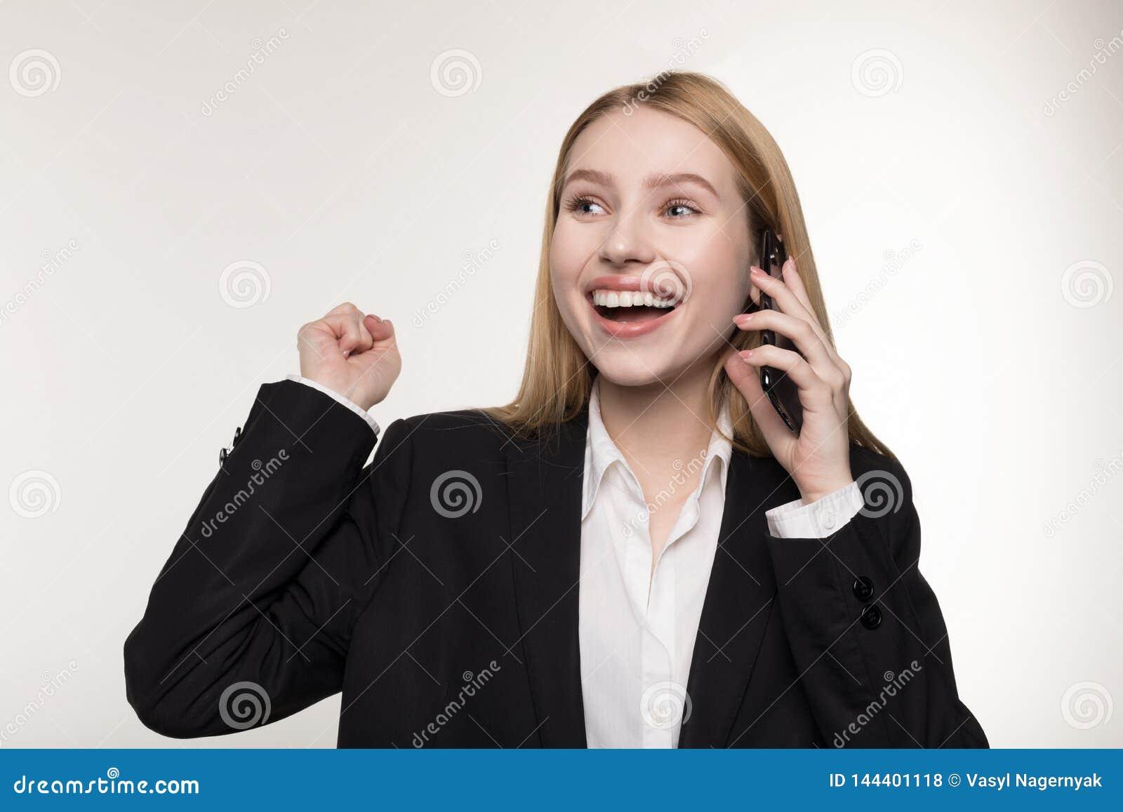 A senhora loura bonita do neg?cio no terno preto est? falando no telefone celular e no sorriso