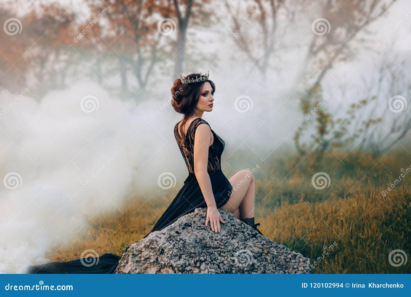 A senhora majestosa, rainha escura, senta-se na pedra que descobre seu pé A menina moreno na coroa gótico E