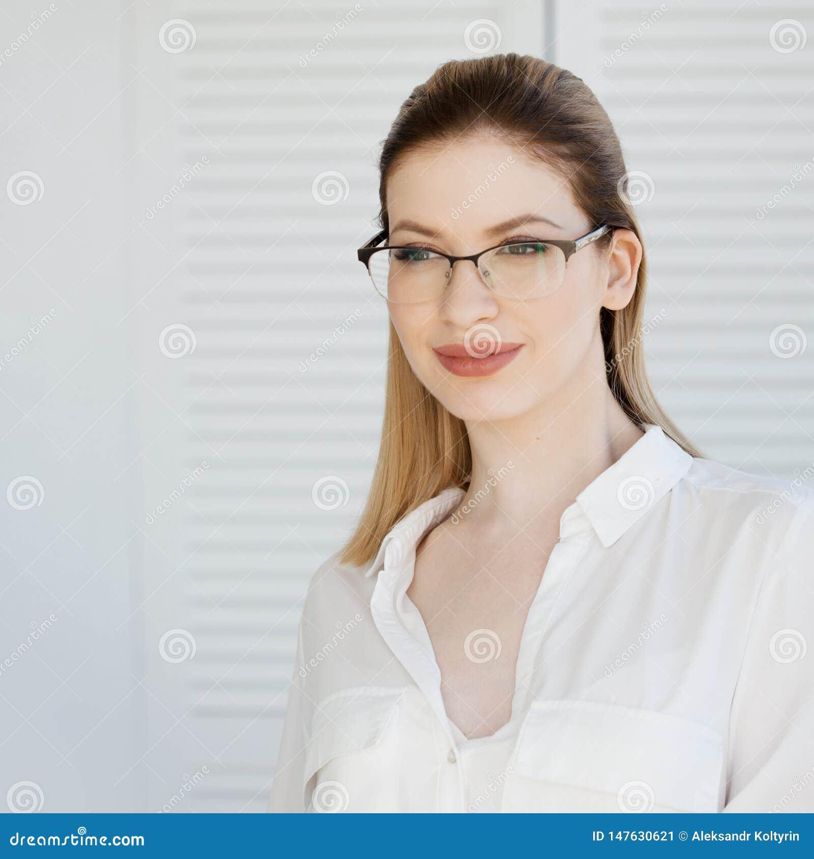 Senhora nova do neg?cio na camisa e nos vidros brancos Sorriso atrativo da mulher nova