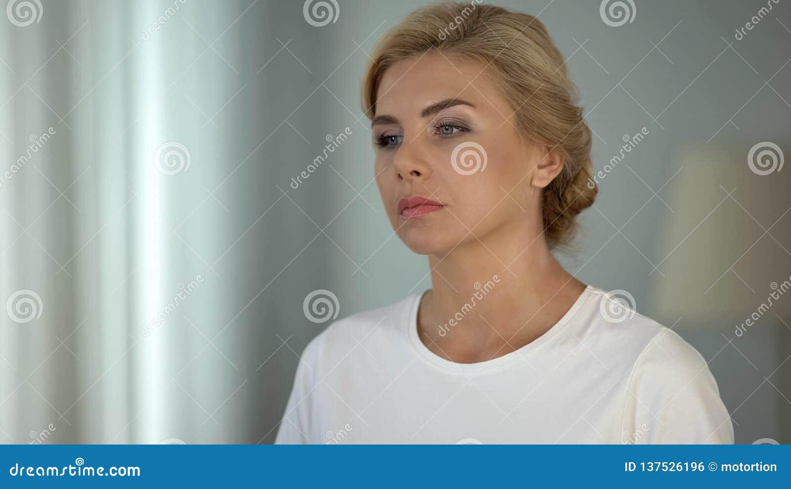 Senhora pensativa louro-de cabelo bonita que pensa sobre a vida, a depressão e os problemas